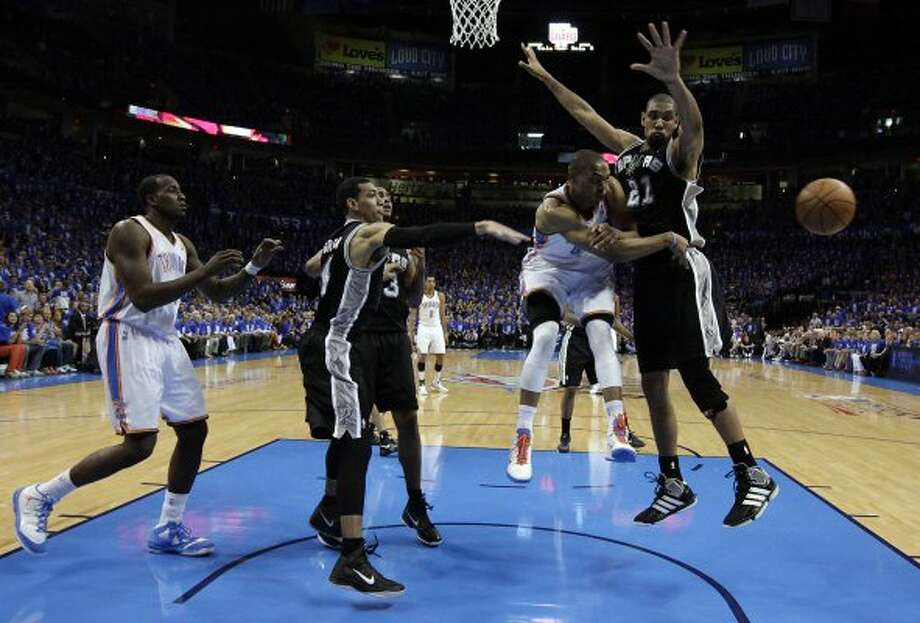 Oklahoma City Thunder's Russell Westbrook (0) passes around San Antonio Spurs' Tim Duncan (21) during the first half of game three of the NBA Western Conference Finals in Oklahoma City, Okla. on Thursday, May 31, 2012. (Kin Man Hui / Kin Man Hui / San Antonio Express-News)