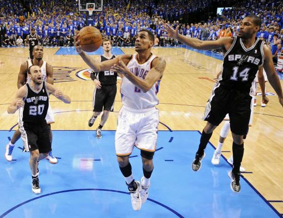 Thunder's Thabo Sefolosha shoots between Spurs' Manu Ginobili and Spurs' Gary Neal during the second half of game three of the NBA Western Conference Finals in Oklahoma City, Okla. on Thursday, May 31, 2012.  The Thunder won 102-82. (Edward A. Ornelas / Edward A. Ornelas / San Antonio Express-News)
