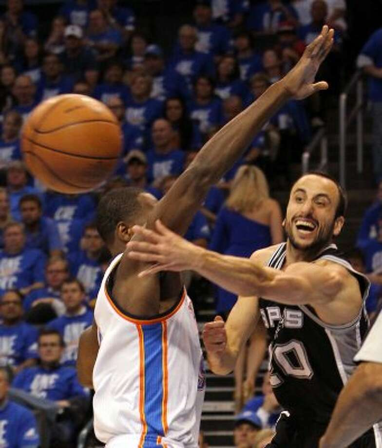 San Antonio Spurs' Manu Ginobili (20) passes around Oklahoma City Thunder's Serge Ibaka (9) during the first half of game three of the NBA Western Conference Finals in Oklahoma City, Okla. on Thursday, May 31, 2012. (Kin Man Hui / Kin Man Hui / San Antonio Express-News)