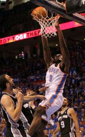 Oklahoma City Thunder's Serge Ibaka (9) dunks over San Antonio Spurs' Stephen Jackson (3) and San Antonio Spurs' Manu Ginobili (20) during the second half of game three of the NBA Western Conference Finals in Oklahoma City, Okla. on Thursday, May 31, 2012. (Kin Man Hui / Kin Man Hui / San Antonio Express-News)