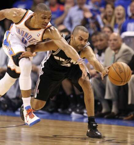 San Antonio Spurs' Tony Parker (9) and Oklahoma City Thunder's Russell Westbrook (0) reach for a loose ball during the first half of game three of the NBA Western Conference Finals in Oklahoma City, Okla. on Thursday, May 31, 2012. (Edward A. Ornelas / Edward A. Ornelas / San Antonio Express-News)