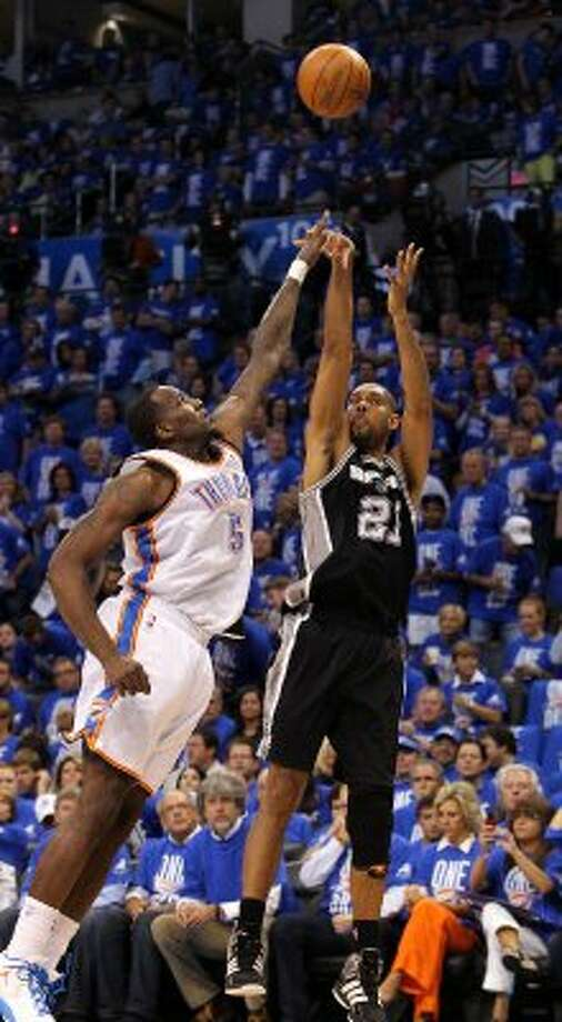 San Antonio Spurs' Tim Duncan (21) shoots over Oklahoma City Thunder's Kendrick Perkins (5) during the first half of game three of the NBA Western Conference Finals in Oklahoma City, Okla. on Thursday, May 31, 2012. (Kin Man Hui / Kin Man Hui / San Antonio Express-News)