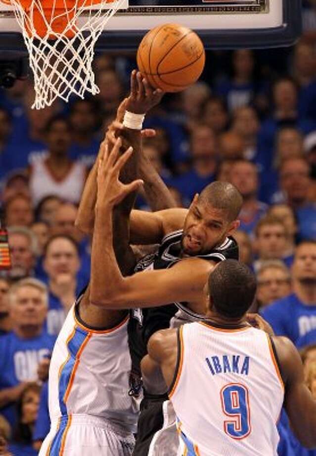 San Antonio Spurs' Tim Duncan (21) pulls in a rebound against Oklahoma City Thunder's Kendrick Perkins and Oklahoma City Thunder's Serge Ibaka (9) during the first half of game three of the NBA Western Conference Finals in Oklahoma City, Okla. on Thursday, May 31, 2012. (Kin Man Hui / Kin Man Hui / San Antonio Express-News)