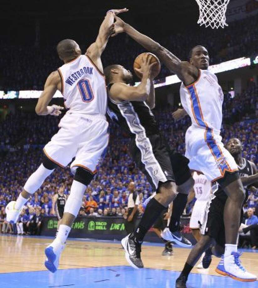 San Antonio Spurs' Gary Neal (14) shoots under pressure from Oklahoma City Thunder's Russell Westbrook (0) and Oklahoma City Thunder's Serge Ibaka (9) during the second half of game three of the NBA Western Conference Finals in Oklahoma City, Okla. on Thursday, May 31, 2012. (Edward A. Ornelas / Edward A. Ornelas / San Antonio Express-News)