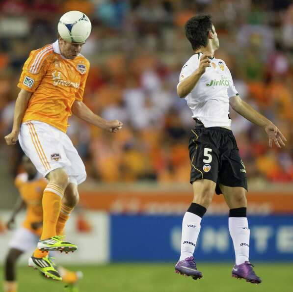 Houston Dynamo midfielder Brian Ownby (22) wins a header against Valencia midfielder Alert Dalmau (5