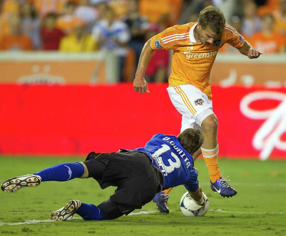 Valencia goalkeeper Vicente Guaita (13) makes a stop against Houston Dynamo forward Colin Rolfe (14) right in front to the net during stoppage time at the end of the BBVA Compass Dynamo Charities Cup friendly soccer match on Thursday, May 31, 2012, at BBVA Compass Stadium in Houston. Valencia won the game 2-1. Photo: Smiley N. Pool, Houston Chronicle / © 2012  Houston Chronicle