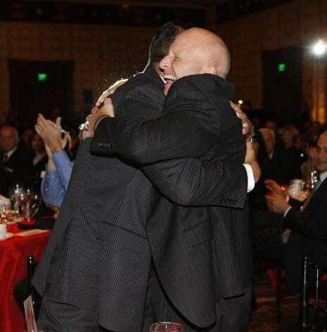 Harlandale ISD Superintendent Robert Jaklich (right) hugs Board President Anthony Alcoser after the district won the Large District category of the 10th annual H-E-B Excellence in Education Awards in Austin on May 15, 2011. (Jerry Lara / San Antonio Express-News)