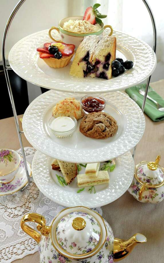 An Afternoon Tea setup on Friday, May 25, 2012, at Tailored Tea in Latham, N.Y. The top tier features a lemon and blueberry cake, a fruit tart and rice pudding. The second has a bacon and cheddar scone and a chocolate expresso scone served with clotted cream and jam. The bottom tier holds tea sandwiches including smoked salmon with scallions, cucumber mascarpone and egg salad. (Cindy Schultz / Times Union) Photo: Cindy Schultz / 00017830A