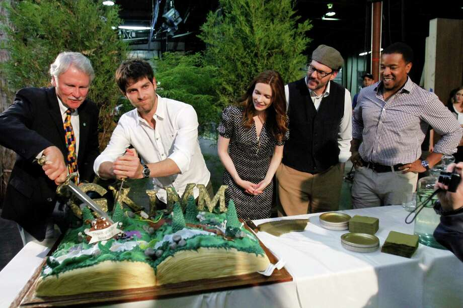 Oregon Gov. John Kitzhaber, left, prepares to cut a cake with help from Grimm cast members, from left, David Giuntoli, Bitsie Tulloch, Silas Weir Mitchell and Russell Hornsby 1during the kickoff party of second season production for their NBC television series in Portland, Ore., Tuesday, May 29, 2012.  Grimm is filmed in Portland.(AP Photo/Don Ryan) Photo: Don Ryan, Associated Press / AP
