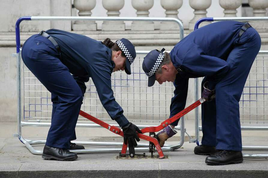 Two police officers examine beneath a manhole cover on Whitehall on June 1, 2012 in London, En