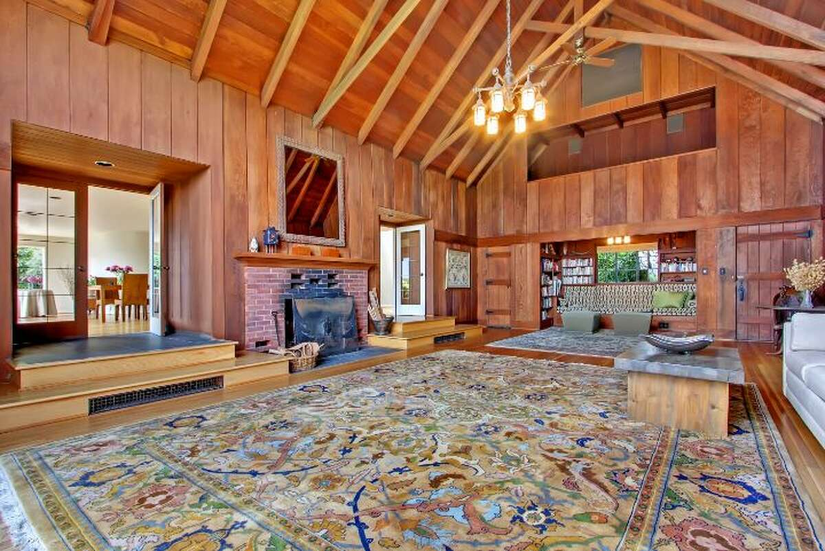 Great room, with wood walls, a beamed cathedral ceiling and a substantial brick fireplace, of 625 Hillside Drive E., was built in 1923 by the renowned Seattle architect Paul Thiry. The house is now 3,750 square feet, with five bedrooms, 2.5 bathrooms, large decks, a studio apartment above a three-car garage, expansive views of Lake Washington and beyond and planting beds on nearly one-third of an acre. It's listed for $1.795 million.
