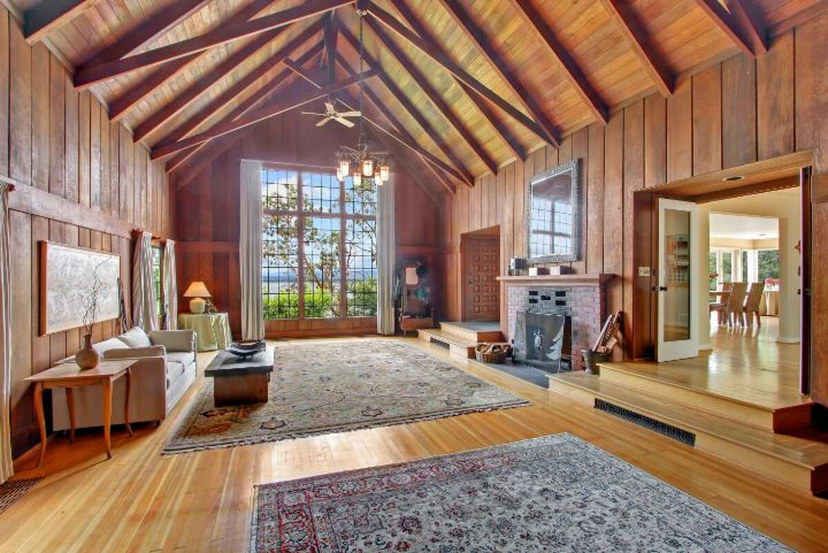"""Here's a home that gives new meaning to the idea of a """"great room."""" The original part of the house, at 625 Hillside Drive E., was built in 1923 by the renowned Seattle architect Paul Thiry and features wood walls, a beamed cathedral ceiling and a substantial brick fireplace. The house is now 3,750 square feet, with five bedrooms, 2.5 bathrooms, large decks, a studio apartment above a three-car garage, expansive views of Lake Washington and beyond and planting beds on nearly one-third of an acre. It's listed for $1.795 million."""