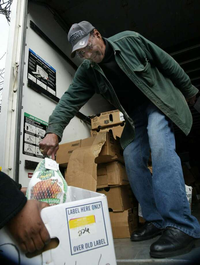 Arthur West Sr, passes out turkeys from The Kings Pantry at 30 Florence Street, a program within Healing Tree Economic Development Inc. in Bridgeport. Tuesday, Nov. 14, 2009. Photo: Phil Noel / Connecticut Post