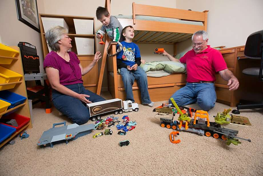 John and Debbie Button play with their grandchildren Anthony Ramirez, 5,lf, and Ezra Zion Dickey, 10, in a room they set up for their grandchildren in their Paso Robles home. The Buttons sold their million dollar home in Danville to buy one half the price on a bigger lot in Paso Robles, where they now own a chocolate shop. Their grandkids live three blocks away and are a big part of their lives. John who worked in high tech, is semi-retired, and likes to ride his motorcycles on the backroads of Paso Robles and up and down the coast. Debbie really likes working at the chocolate shop which they purchased after moving to Paso Robles. Photo: Tomas Ovalle, Special To The Chronicle