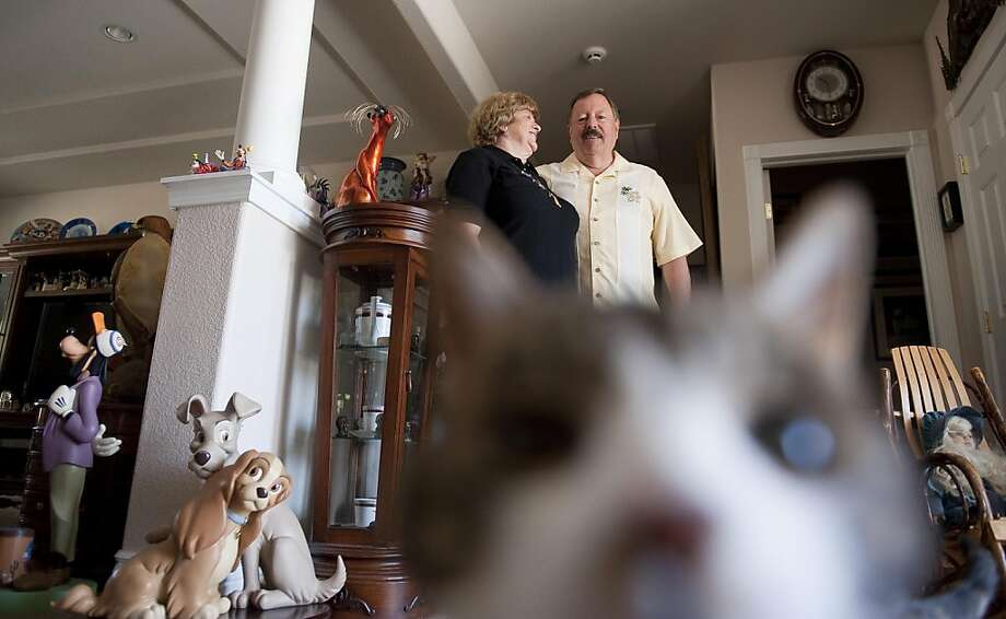 Marty and Linda Martin stand near their collection of Disney figures while their cat examines the camera inside their home Tuesday, May 8, 2012 in Gardnerville, Nevada.   The Martins moved from San Jose to Gardnerville which is 10 miles south of Carson City. Photo By: Liz Margerum Photo: Liz Margerum