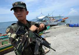 A Philippine soldier stands guard next to fishing boats (back) at a pier in Masinloc town, Zambales province, 230 kilometres (140 miles) from Scarborough Shoal on May 18, 2012, which protesters were to board and set sail to the disputed shoal. Philippine President Benigno Aquino told protesters to abort plans to sail May 18, to a disputed South China Sea shoal also claimed by China, the leader of the group said.         AFP PHOTO/TED ALJIBETED ALJIBE/AFP/GettyImages