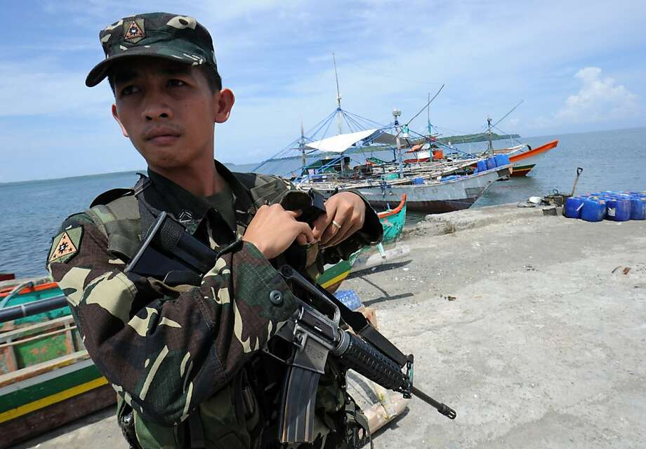 A Philippine soldier stands guard next to fishing boats (back) at a pier in Masinloc town, Zambales province, 230 kilometres (140 miles) from Scarborough Shoal on May 18, 2012, which protesters were to board and set sail to the disputed shoal. Philippine President Benigno Aquino told protesters to abort plans to sail May 18, to a disputed South China Sea shoal also claimed by China, the leader of the group said.         AFP PHOTO/TED ALJIBETED ALJIBE/AFP/GettyImages Photo: Ted Aljibe, AFP/Getty Images