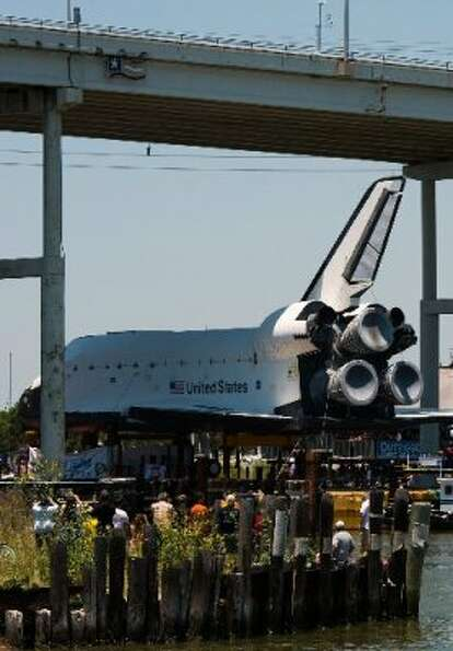 A full-size replica of the space shuttle passes the under Texas 146 bridge on Friday, June 1, 2012,