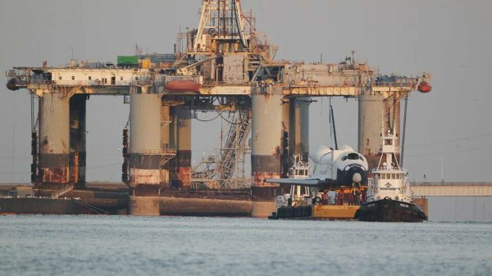 A space shuttle mock-up is moved on a barge through the Galveston Ship Channel on its way to Space C