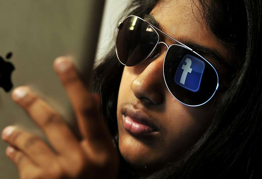 The 'Facebook' logo is reflected in a young Indian woman's sunglasses as she browses on a tablet in Bangalore on May 15, 2012.  World's popular and leading social networking company Facebook Inc., founded in a Harvard dorm room by Mark Zuckerberg whose current value exceeds 100 billion USD, will be making an initial public offering (IPO) which is slated to be Silicon Valley's biggest-ever.    AFP PHOTO/ TOPSHOTS/ MANJUNATH KIRANManjunath Kiran/AFP/GettyImages Photo: Manjunath Kiran, AFP/Getty Images