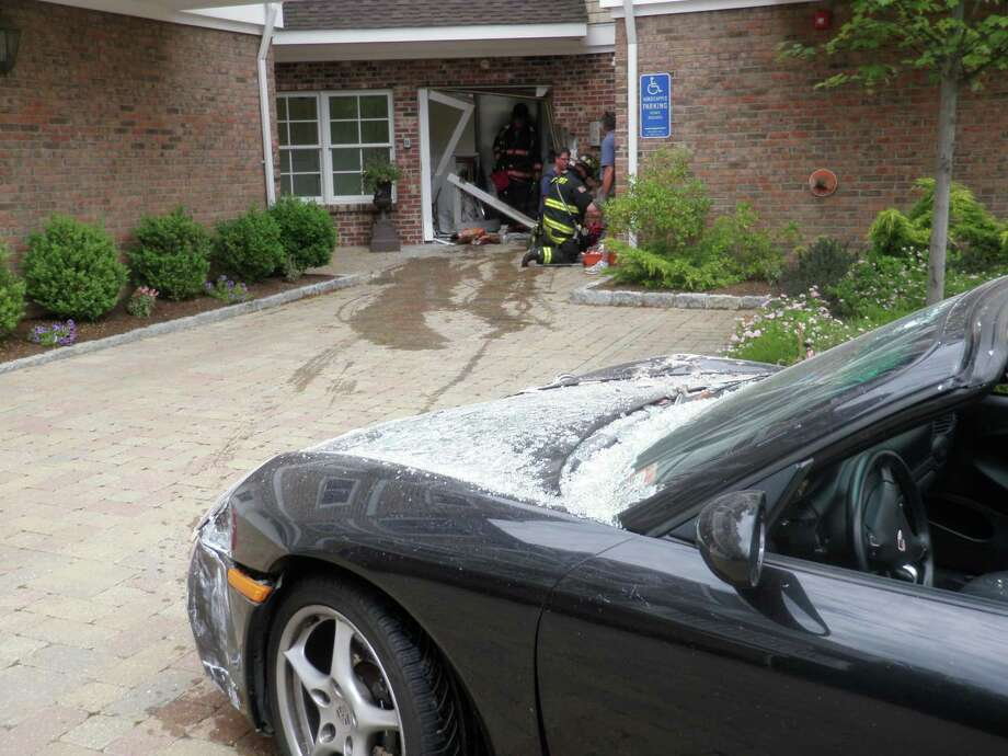 This driver of this Porsche lost control of the vehicle and smashed into the entryway of a Post Road West condominium complex Friday afternoon. Photo: Westport Fire Department / Westport News contributed