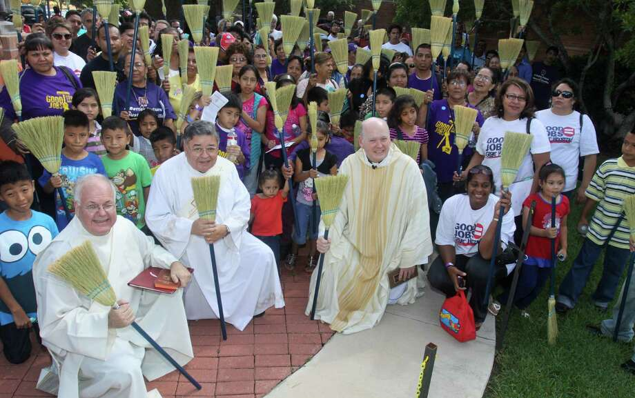 "Deacon Sam Dunning, left, Deacon Joseph Rubio and Rev. Brendan Cahill, chancellor of the Houston-Galveston Archdiocese, participate in a ""blessing of the brooms"" mass with local janitors. Photo: Gary Fountain / Copyright 2012 Gary Fountain."