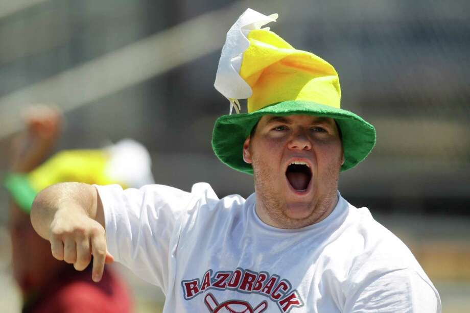 "An Arkansas fan dons a ""rally"" hat as he cheers on the team in the 7th inning during a college baseball game at the Houston Regional at Rice University, Friday, June 1, 2012, in Houston. Arkansas won the game against Sam Houston 5-4. Photo: Karen Warren, Houston Chronicle / © 2012  Houston Chronicle"