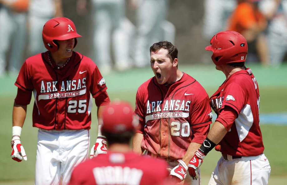 Arkansas' Matt Vinson (20) celebrates after sliding into home against Sam Houston's catcher John Hale (10) on an RBI by Tim Carver (18) in the 7th inning during a college baseball game at the Houston Regional at Rice University, Friday, June 1, 2012, in Houston. Arkansas won the game against Sam Houston 5-4. Photo: Karen Warren, Houston Chronicle / © 2012  Houston Chronicle
