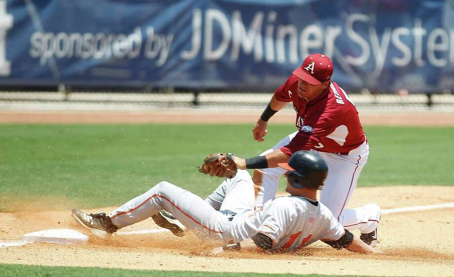 Arkansas 3B Matt Reynolds (5) tags out Sam Houston's Colt Atwood (11) at third base in the 3rd inning during a college baseball game at the Houston Regional at Rice University, Friday, June 1, 2012, in Houston. Arkansas won the game against Sam Houston 5-4. Photo: Karen Warren, Houston Chronicle / © 2012  Houston Chronicle
