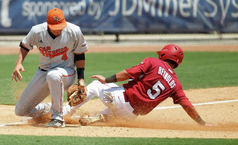 Sam Houston's 3B Kevin Miller (4) tries to apply the tag to Arkansas' Matt Reynolds (5) at third in the 4th inning during a college baseball game at the Houston Regional at Rice University, Friday, June 1, 2012, in Houston. Arkansas won the game against Sam Houston 5-4. Photo: Karen Warren, Houston Chronicle / © 2012  Houston Chronicle