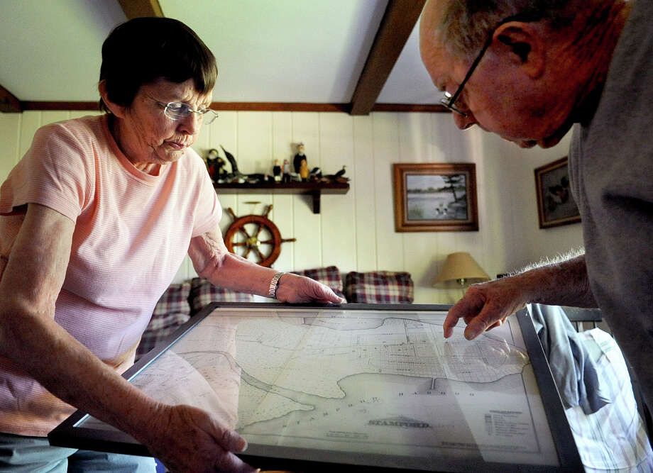 Nancy and George Smith look at an old map of Shippan at their home in Stamford on Thursday, May 31, 2012. Photo: Lindsay Niegelberg / Stamford Advocate