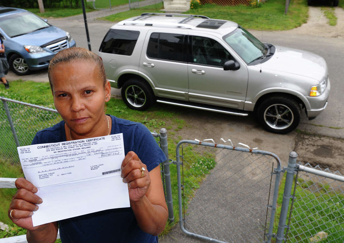 Farash Martinez holds up one of her vehicle registration certificates that proves she is a resident of Stratford, at her home on Allen Street in Stratford, Conn. on Friday June 1, 2012. Matinez had a book placed onto the Ford Explorer behind her and was told she owed Bridgeport overdue taxes, but her complaints about being a resident of Stratford fell on deaf ears.