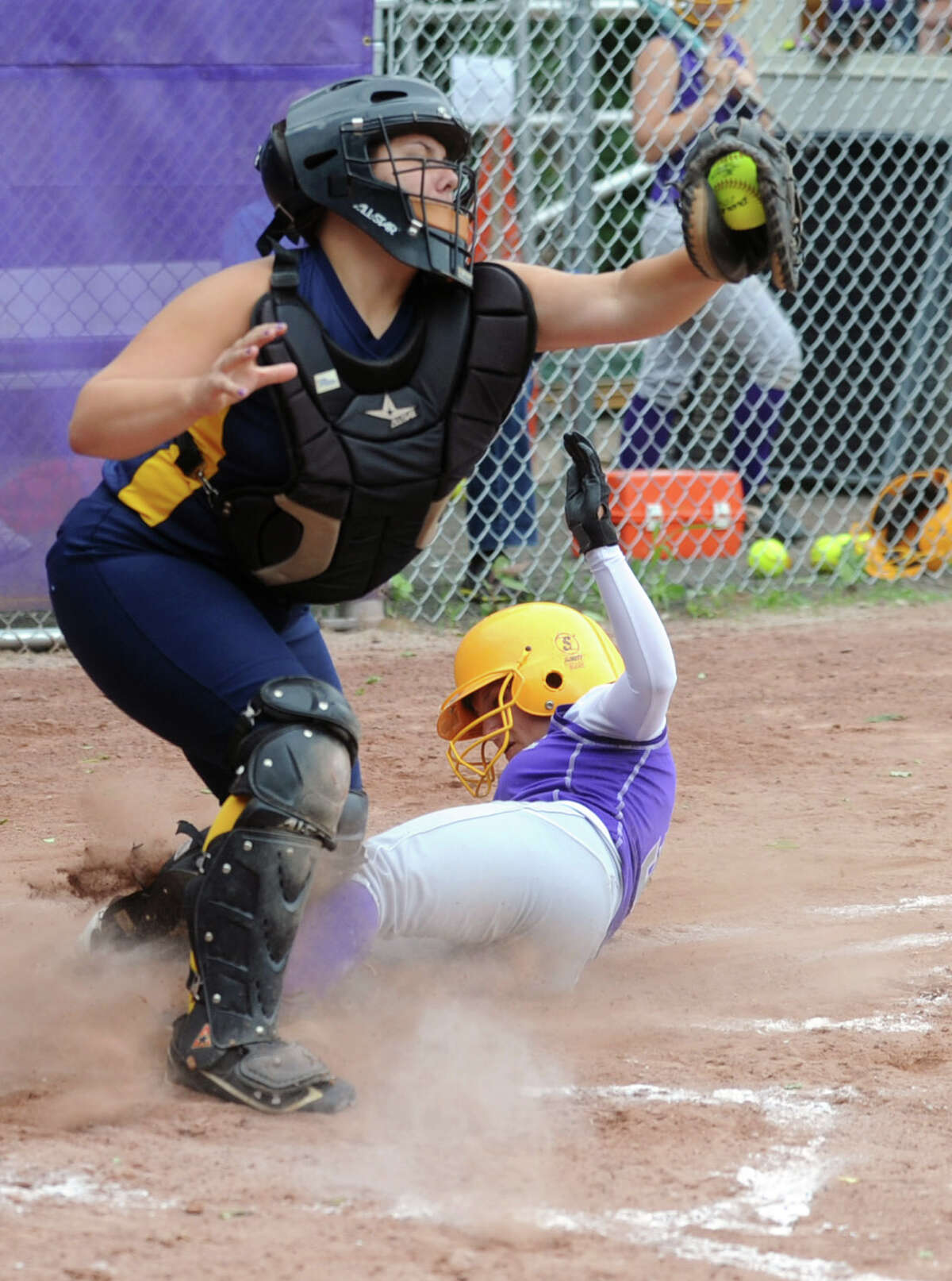Westhill's Allyson Souza scores a run as she slides safely into home while Mercy's catcher Tyler Keegan reaches for the ball during Friday's softball game against Mercy in Stamford on June 1, 2012.