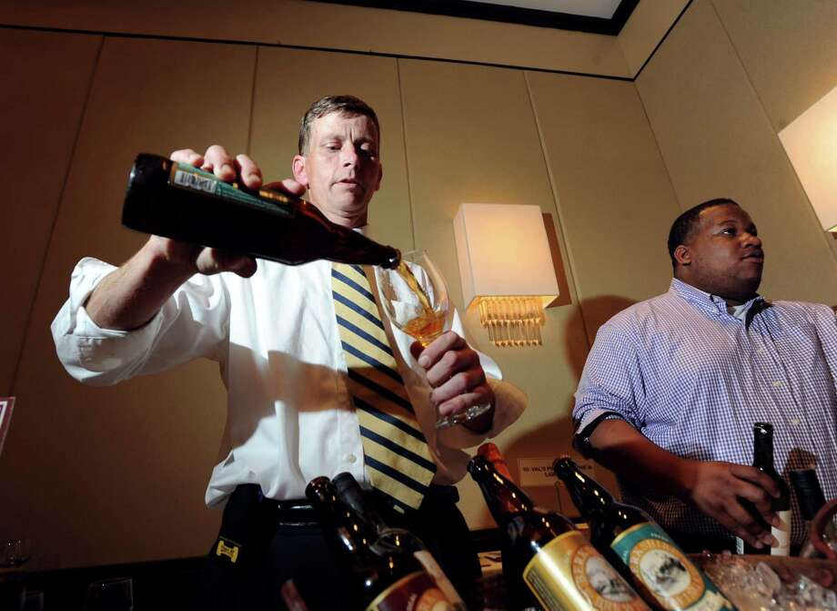 At left, Brian Doud of Val's Putnam Wines & Liquors of Greenwich, pours a craft beer for a patron during the Greenwich Chamber of Commerce Business & Culinary Showcase at Hyatt Regency Greenwich, Thursday, May 31, 2012. Photo: Bob Luckey / Greenwich Time