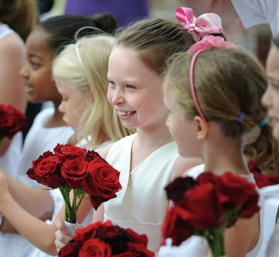 Flower girl Regina Finn, 8, smiles during the Convent of the Sacred Heart graduation in Greenwich, Friday, June 1, 2012. Photo: Bob Luckey / Greenwich Time