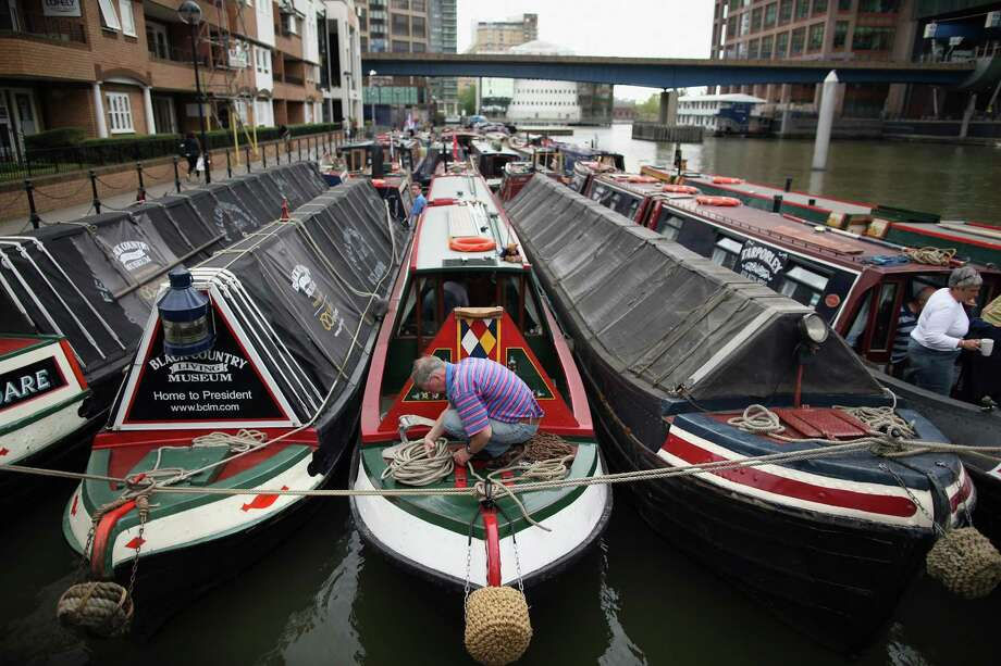 A man puts the finishing touches to his barge at South Quay, where many of the boats are moored ahead of taking part in the Queen's Diamond Jubilee River Pageant on June 1, 2012 in London, England. With two days to go before the start of Diamond Jubilee celebrations final preparations are taking place in the capital. Photo: Dan Kitwood, Getty Images / 2012 Getty Images