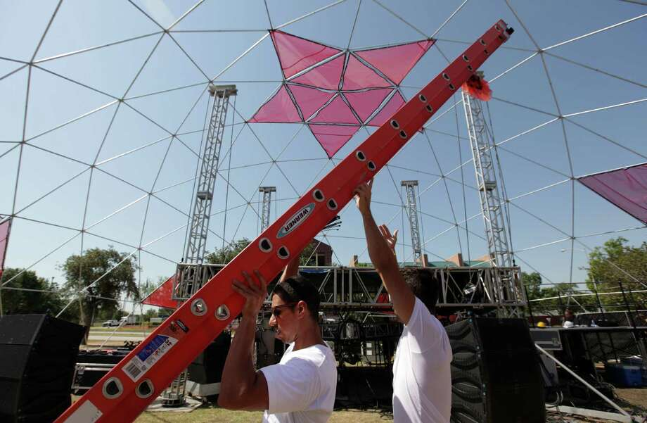 Shahkoh Sohail and Monir Yari set up ladder to finish assembling dome as crews prepare for Free Press Summer Fest on Friday, June 1, 2012, in Houston.  Summer Fest starts June 2-3 along Allen Parkway, and concert goers can expect humid, sunny, rain free weather. Photo: Mayra Beltran, Houston Chronicle / Houston Chronicle
