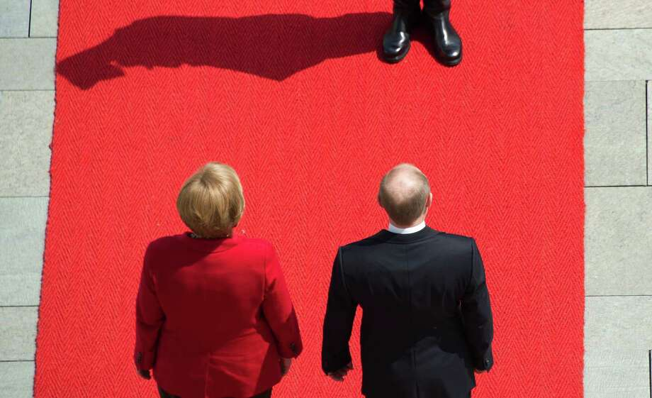 German Chancellor Angela Merkel, left, and Russian President Vladimir Putin, right, review a guard of honours on Friday at the Chancellery in Berlin, before a meeting for his first trip to Germany since returning as leader of Russia. Photo: JOHANNES EISELE / AFP