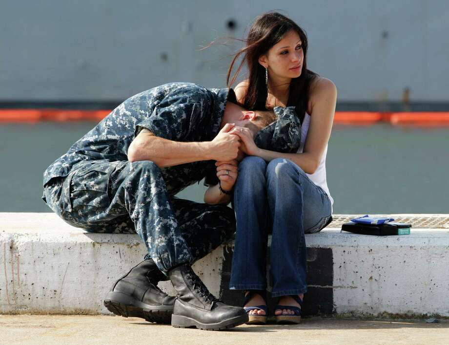 U.S. Navy Gunners Mate, Steven Joyce, puts his head in the lap of his wife, Damara, as he says good bye as his ship the USS Carr prepares to depart Naval Station Norfolk en route to the Persian Gulf in Norfolk, Va., Friday, June 1, 2012.  The ship is part of the group leaving with the floating special operations base ship USS Ponce for deployment to the Persian Gulf. Photo: Steve Helber, Associated Press / AP