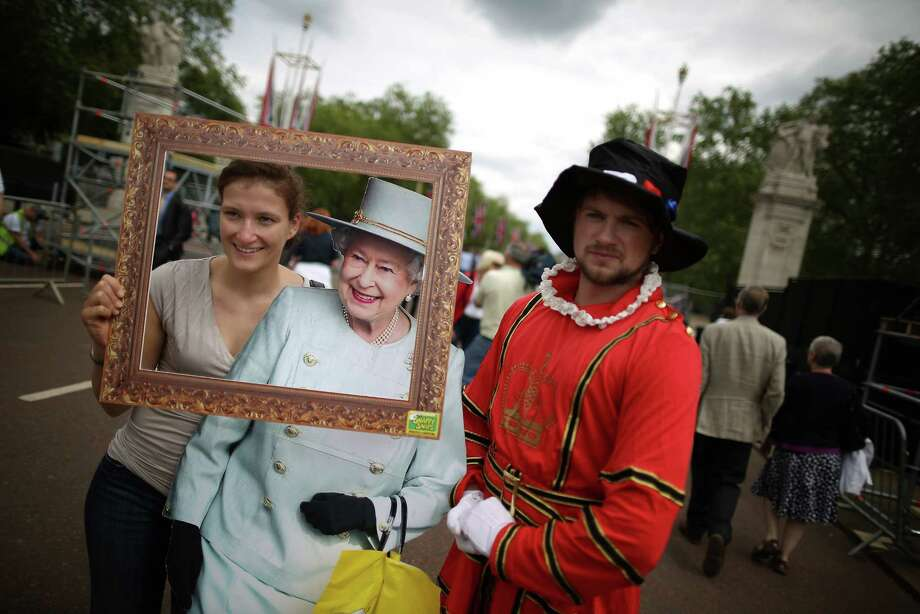 A tourist has her photograph taken with a cardboard cutout of Queen Elizabeth II in The Mall on Friday, as the start of Diamond Jubilee celebrations nears. Photo: Peter Macdiarmid / 2012 Getty Images