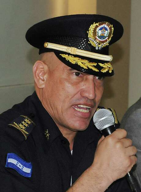 In this May 22, 2012 photo, officer on Juan Carlos Bonilla Valladares, known as ?El Tigre? or ?The Tiger? speaks to the press after he was sworn-in as Honduras' new Chief of Police in Tegucigalpa, Honduras. Bonilla Valladares, the new chief chosen to clean up a Honduran national police force tarred with allegations of corruption and involvement in murders was accused by the department?s internal affairs investigators of running a death squad when he was a top regional police official. (AP Photo/Fernando Antonio) Photo: Fernando Antonio / AP