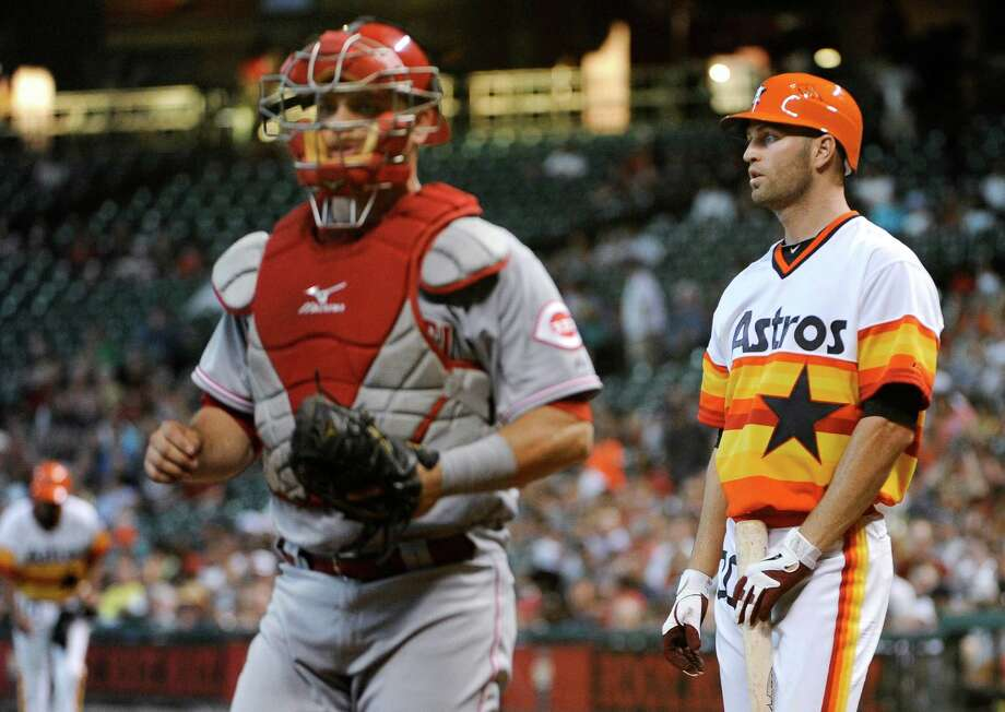 Houston Astros pitcher J.A. Happ, right, stares off after striking out with the bases loaded to end the second inning as Cincinnati Reds catcher Devin Mesoraco heads for the dugout in a baseball game Friday, June 1, 2012, in Houston. Photo: AP
