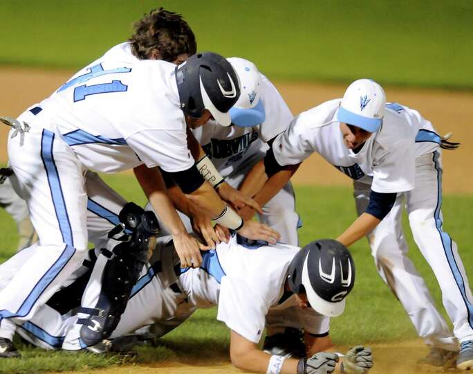 Columbia players pile on top of Anthony Maney (12), who hit in the winning run in the ninth inning,