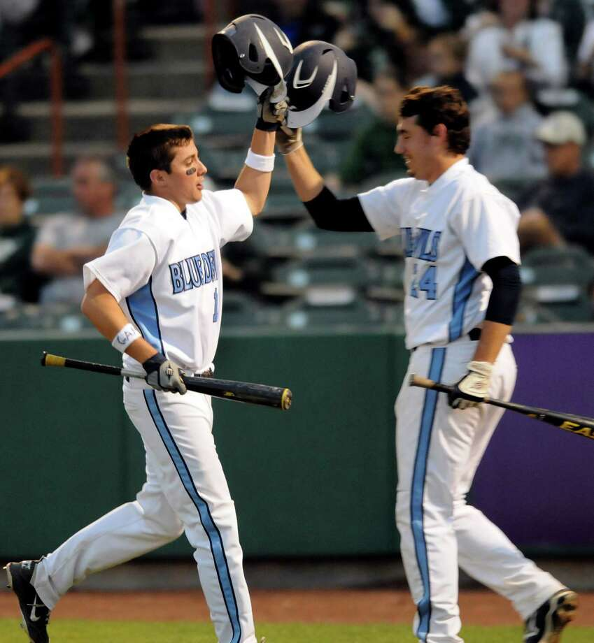 Columbia's Anthony Maney (12), left, scores a run and hits helmets with Timothy Gaule (24) during their Class AA final baseball game against Shenedehowa on Friday, June 1, 2012, at Joseph L. Bruno Stadium in Troy, N.Y. (Cindy Schultz / Times Union) Photo: Cindy Schultz / 00017858A