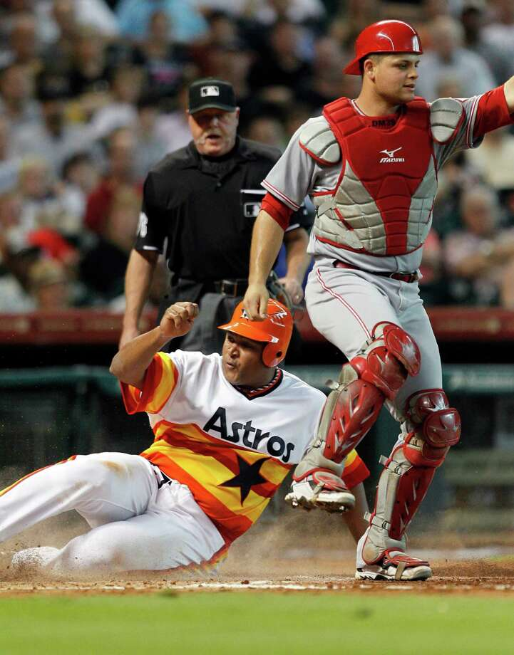 Being forced out at home in the second was only the start of a bad night for Carlos Lee, left, who hit into two double plays, coming up lame on the second one. Photo: Bob Levey / 2012 Getty Images