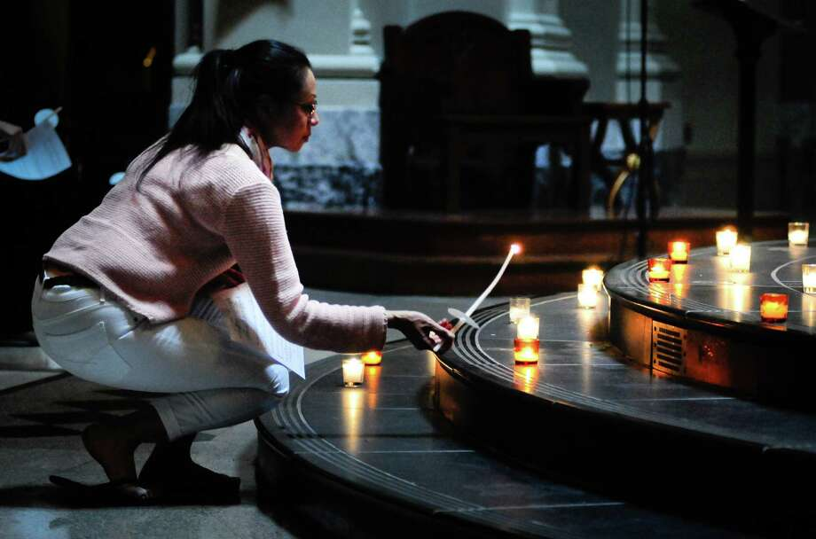 Eloisa Cardona bends down to light her candle during a prayer service at St. James Cathedral for the victims of Wednesday's  shootings on Friday, June 1, 2012. Photo: LINDSEY WASSON, Lindsey Wasson / SEATTLEPI.COM