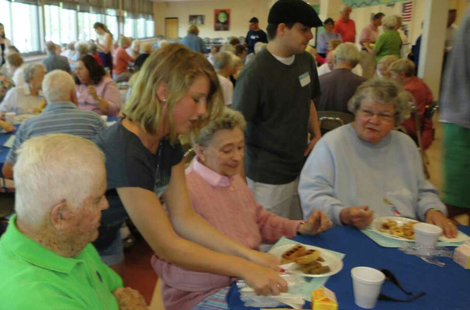 Christie Soule, 17, brought breakfast to the table of several seniors who attended the annual seniors serving seniors event at Fairfield Ludlowe High School on Friday morning. Photo: Meg Barone / Fairfield Citizen freelance