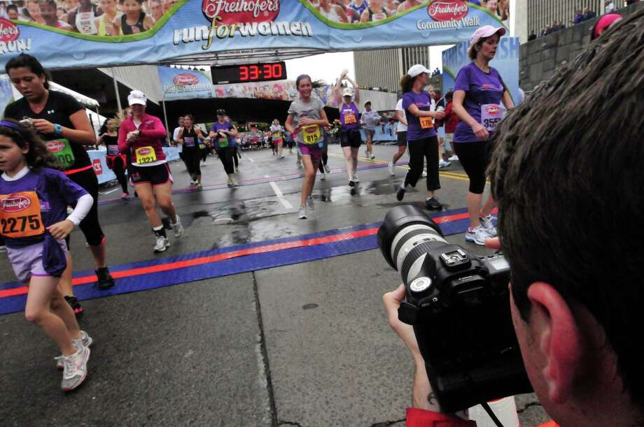 Photographer Patrick Dodson captures runners crossing the finishline during the 34th annual Freihofer's Run for Women in Albany N.Y. Saturday June 2, 2012. (Michael P. Farrell/Times Union) Photo: Michael P. Farrell