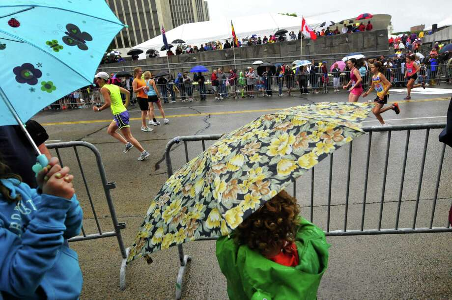 Three-year-old Logen Zabielski of Amsterdam watches under umbrella cover as runners warm up prior to the start of the 34rd annual Freihofer's Run for Women in Albany N.Y. Saturday June 2, 2012. (Michael P. Farrell/Times Union) Photo: Michael P. Farrell
