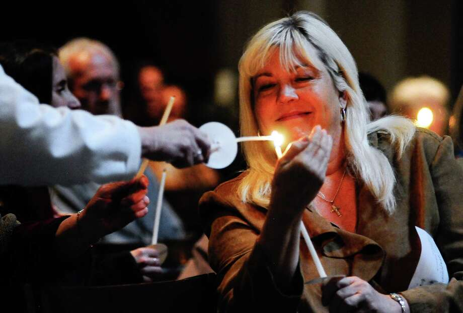 A woman shields her candle as it is lit during a prayer service at St. James Cathedral for the victims of Wednesday's  shootings on Friday, June 1, 2012. Photo: LINDSEY WASSON / SEATTLEPI.COM